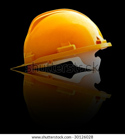 Isolated yellow helmet reflected in a black desk - stock photo