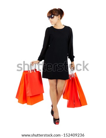 Isolated young asian woman carries shopping bags - stock photo