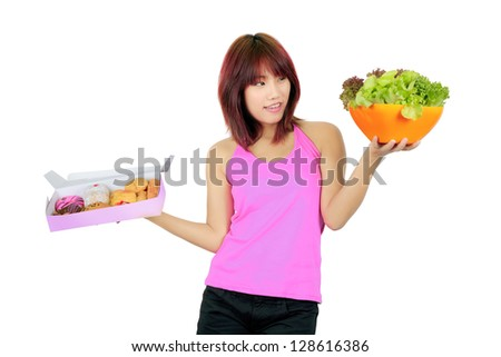 Isolated young asian woman with a box of donut and a bowl of vegetable salad - stock photo