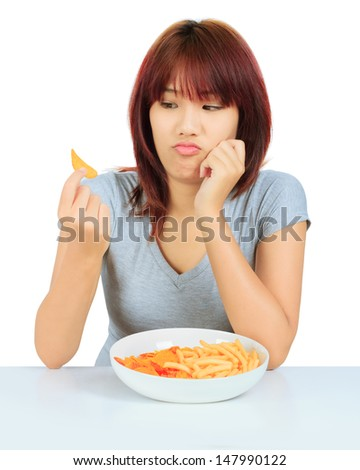 Isolated young asian woman with a plate of potato chips and french fries - stock photo