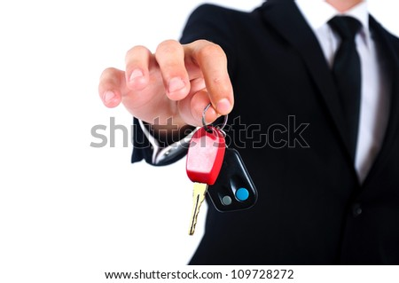 Isolated young business man giving car key - stock photo