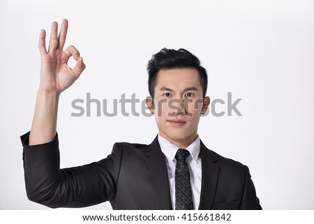 Isolated young business man in suit with ok gesture - stock photo