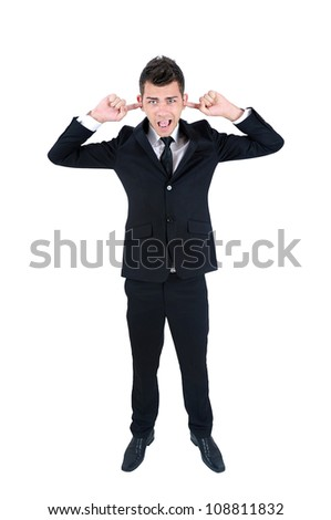 Isolated young business man with ears covered - stock photo