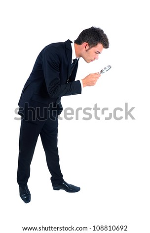 Isolated young business man with magnifying glass - stock photo