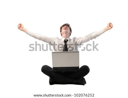 Isolated young businessman triumphing with a laptop on his knees - stock photo