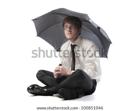 Isolated young businessman under an umbrella - stock photo