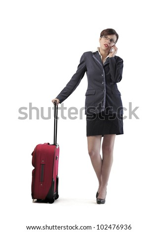 Isolated young businesswoman holding a trolley case and talking on the mobile phone - stock photo