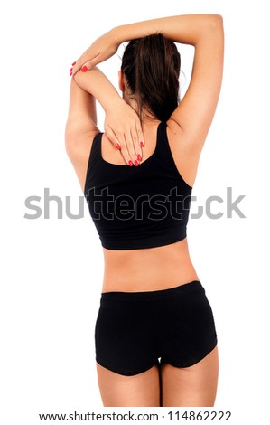 Isolated young fitness woman back touch