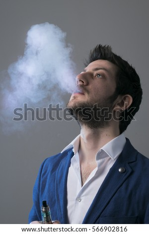 Isolated young man holding an electronic cigarette, vaping device, mod.