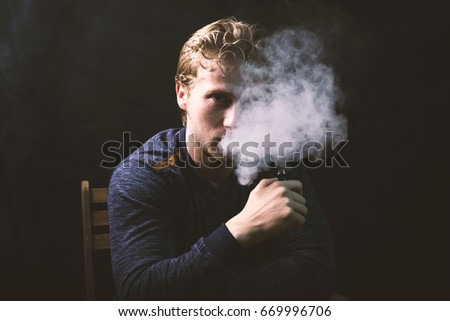 Isolated young man holding and  vaping an electronic cigarette or e cig over a black background.