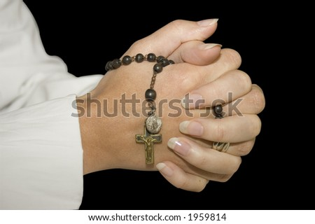 isoled folded hands with rosary. (clipping path included) - stock photo