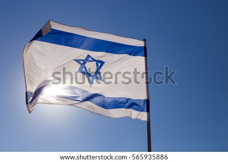 Israel flag close up shot on a background of blue sky. White and blue colors. Israel flag waving against clean blue sky