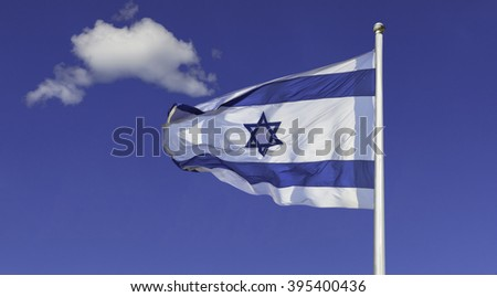 Israel flag flapping in the wind isolated against the blue sky. The flag is on a pole and flapping to the left. there are white clouds in the sky - stock photo