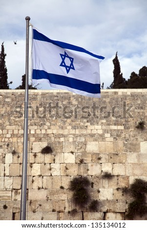 Israel flag fluttering in the wind in front of the holy Wailing Wall, one of the most sacred places to the Jewish people. - stock photo
