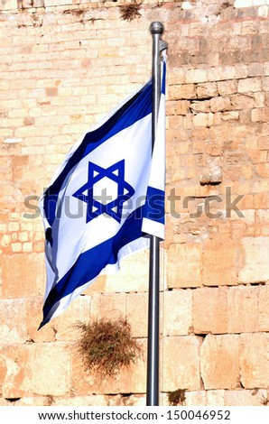 Israel national flag against the Western Wall in Jerusalem, Israel. - stock photo