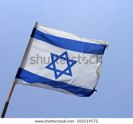 Israel's national flag on blue sky background - stock photo