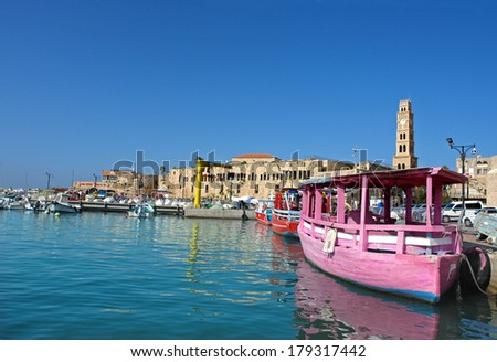 Israel, the ancient port city of Acre, on the docks bright pleasure boats against the backdrop of historic buildings in the Venetian style