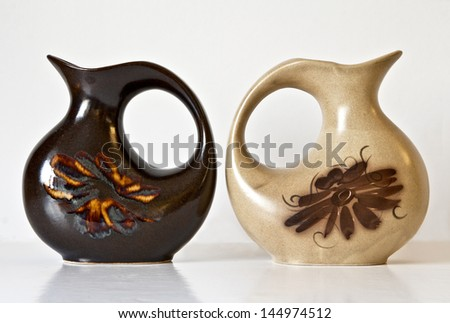 Israeli ceramic pair in  brown tones: two vases of 1950-th years with abstract carved and glazed images.Symbolizes couple: He and She; brother and sister etc. Isolated on white. - stock photo