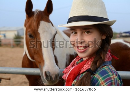 Israeli girl in western clothes (cowgirl) with a horse in a Kibbutz