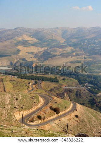Israeli-Jordanian border near the hot springs of Hamat Gader. Serpentine road winds through the green hills