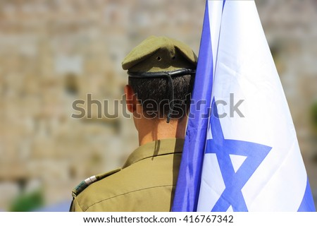 Israeli soldier with flag of Israel on blurred background of Western Wall - stock photo