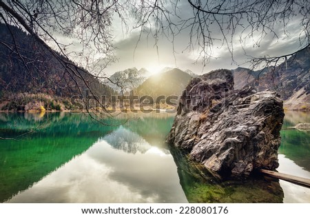 Issyk mountain lake with reflection at sunset sky in Kazakhstan - stock photo
