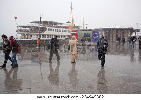 Istanbul,Eminonu,Turkey - January 30, 2012 Some people were trying to walking to the snow at Istanbul A passenger ship was waiting at the pier - stock photo