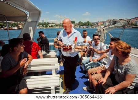 ISTANBUL - JULY 23: Peddler of tea and juice serves drinks and snacks on board the ferry across the Bosphorus on July 23, 2015. With popul. of 14.4 million, Istanbul is the 5th largest city in world  - stock photo