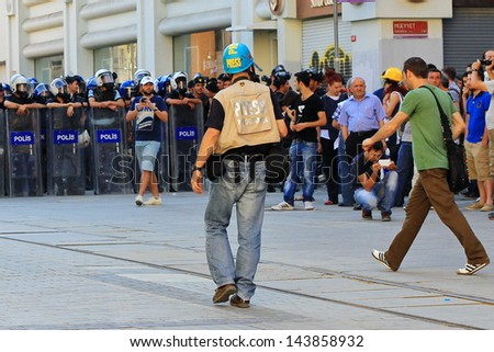 ISTANBUL - JUN 17: Five labor unions call 1-day nationwide strike over crackdown on June 17, 2013 in Istanbul, Turkey. SIPA Press Agency photographer between demonstrators and police line - stock photo