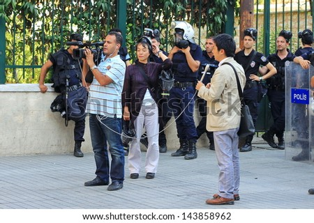 ISTANBUL - JUN 17: Five labor unions call 1-day nationwide strike over crackdown on June 17, 2013 in Istanbul, Turkey. International journalists report live in front of police line at Istiklal Street - stock photo