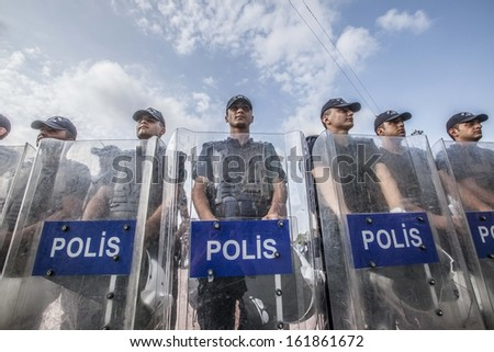 ISTANBUL - JUNE 20: Police stand guard with riot shields during demonstrations against the government in Taksim Square on June 20, 2013 in Istanbul. - stock photo