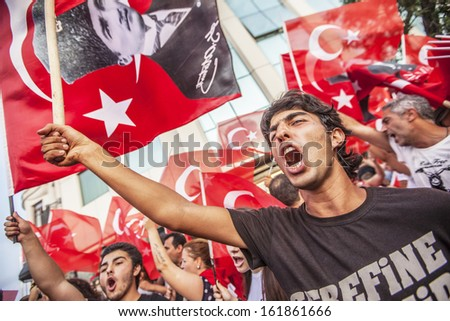 ISTANBUL - JUNE 28: Protesters yell and wave Turkish flags during demonstrations against the government in Taksim Square on June 28, 2013 in Istanbul.  - stock photo