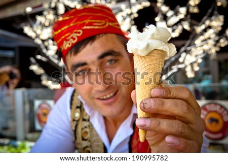 ISTANBUL - MAY 17 - Popular Turkish ice-cream vendor hands over a cone of ice-cream after performing playful tricks on May 17, 2011 in Istanbul. - stock photo