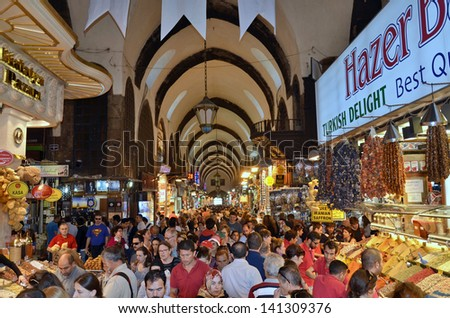 ISTANBUL - MAY 04: Tourists visiting Egyptian Bazaar (Spice Bazaar) on May 04, 2013 in Istanbul, Turkey. Located in Eminonu against Galata is the second largest covered shopping complex   - stock photo