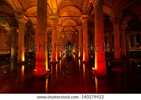 ISTANBUL - MAY 1: Tourists walking in a symmetrical shot of the illuminated Basilica Cistern, the largest of several hundred ancient cisterns that lie beneath the city, Istanbul, Turkey, MAY 1, 2013