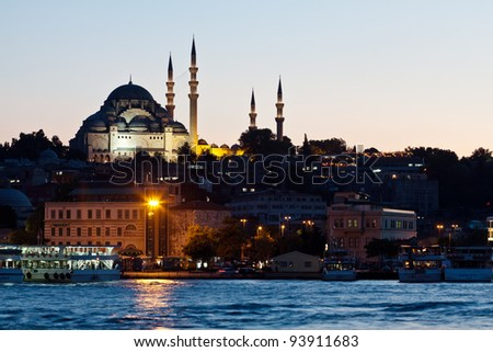 Istanbul skyline from Galata bridge by night, with Suleymaniye mosque and fish boat restaurants in Eminonu - stock photo