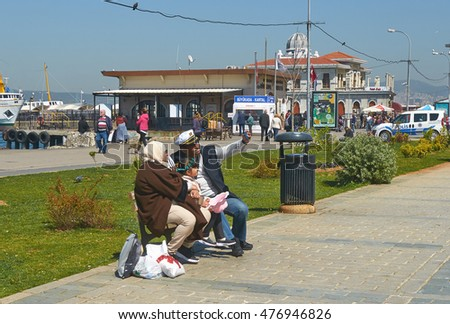 Istanbul, Turkey - April, 04, 2016, Buyukada promenade, family from Middle East is waiting for the start of his trip on a boat, on background of the pier, slice of life, editorial.