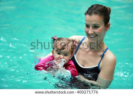 ISTANBUL, TURKEY - APRIL 16: Newborn kids and moms learning swim theraphy in the swimming pool on April 16, 2013 in Istanbul, Turkey. - stock photo