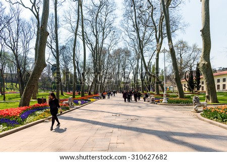 ISTANBUL,TURKEY - APRIL 08, 2015: Tourists in a garden near Sultanahmet square. The Sultanahmet square is the popular tourist place with the numerous landmarks and museums. - stock photo
