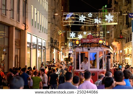 ISTANBUL, TURKEY - AUGUST 2, 2014 : Night view of the famous and historic Red Tram on Istiklal street in Istanbul through a crowd of pedestrians. The Red Tram running between Taksim and Tunel square. - stock photo