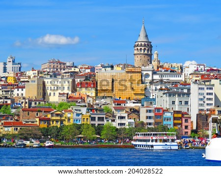 ISTANBUL, TURKEY -- CIRCA APRIL 2014: Galata Tower surrounded by modern buildings - stock photo