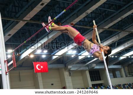 ISTANBUL, TURKEY - DECEMBER 27, 2014: Athlete Demet Parlak pole vaulting during Athletics record attempt races in Asli Cakir Alptekin Athletics hall, Istanbul. - stock photo