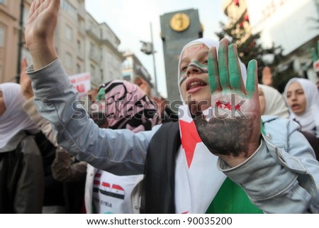 ISTANBUL,TURKEY-DECEMBER 2: Unidentified Syrians living in Istanbul protest the regime of Bashar Essad in front of Syrian Consulate on December 2, 2011 in Istanbul,Turkey. - stock photo