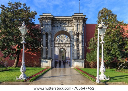 ISTANBUL, TURKEY -FEB 1, 2013: Tourists at the Baroque Architecture gate of Dolmabahce Palace. Dolmabahce is the largest palace in Turkey and one of the most glamorous palaces in the world.