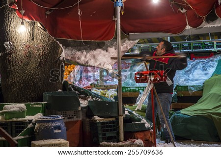 ISTANBUL, TURKEY - FEBRUARY 18, 2015: After heavy snow fall the turkish market owner cleans his booth from the snow on his tent like roof. - stock photo