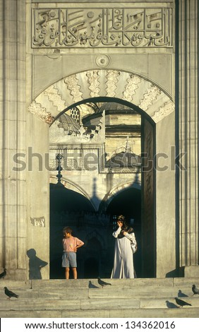 ISTANBUL,TURKEY- JULY 18: A woman coming from the mosque on July 18, 2000 in Istanbul,Turkey. Istanbul is known for great architecture of the local mosques