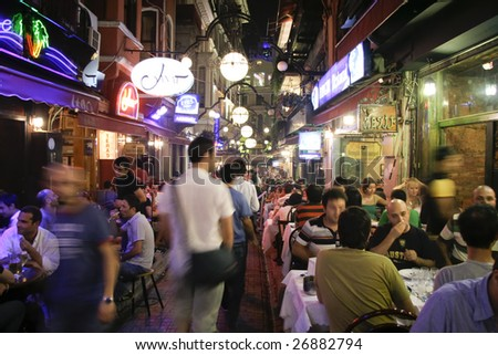 ISTANBUL, TURKEY - JULY 25 : Busy restaurant and bar scene at night in Taksim, Istanbul, Turkey on July 25, 2007. Taksim is a popular destination for tourists and locals of Istanbul. - stock photo