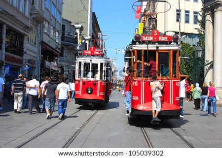 ISTANBUL, TURKEY - JULY 3 : Two trams sit side by side in Taksim Istiklal Street on July 3, 2009 in Istanbul, Turkey. Taksim Istiklal Street is one of the popular destinations in Istanbul. - stock photo