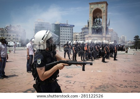 Istanbul, Turkey - June 11, 2013: A riot police officer shoots a gas canister at protesters in Taksim Square. - stock photo