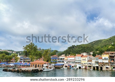 ISTANBUL, TURKEY, JUNE 8, 2013 : Coastline of Anadolu Kavagi, a famous fishing town at the edge of  Bosphorus with many restaurants and touristic facilities. Yoros Castle can be seen at hilltop - stock photo